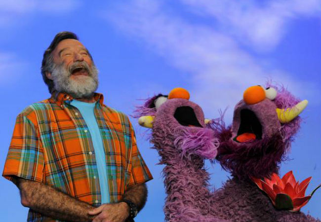"""Robin Williams as I will always remember him - manically laughing, an endlessly entertaining man of unrivalled comic energy; he is pictured in a photo released by Sesame Street via their Twitter account which simply and beautifully said: """"We mourn the loss of our friend Robin Williams, who always made us laugh and smile."""""""