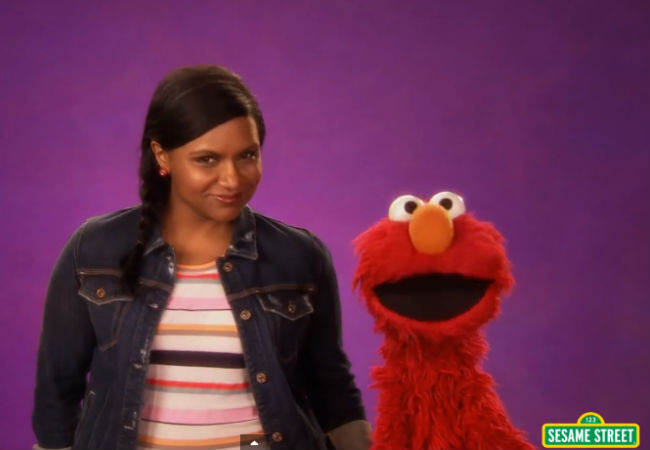 Mindy Kaling and Elmo LOVE the idea of being together AND dancing! (Image via YouTube (c) Childrens' Television Workshop)